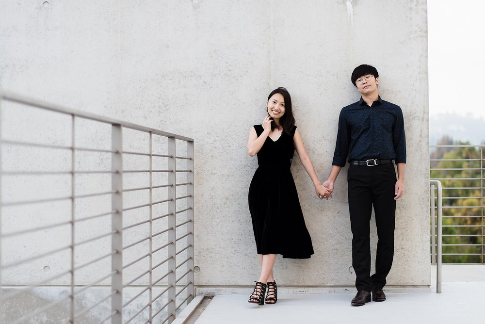 artistic graduation senior portrait with a fashionable chinese couple standing in front of a gray wall and gray setting at ucla in los angeles