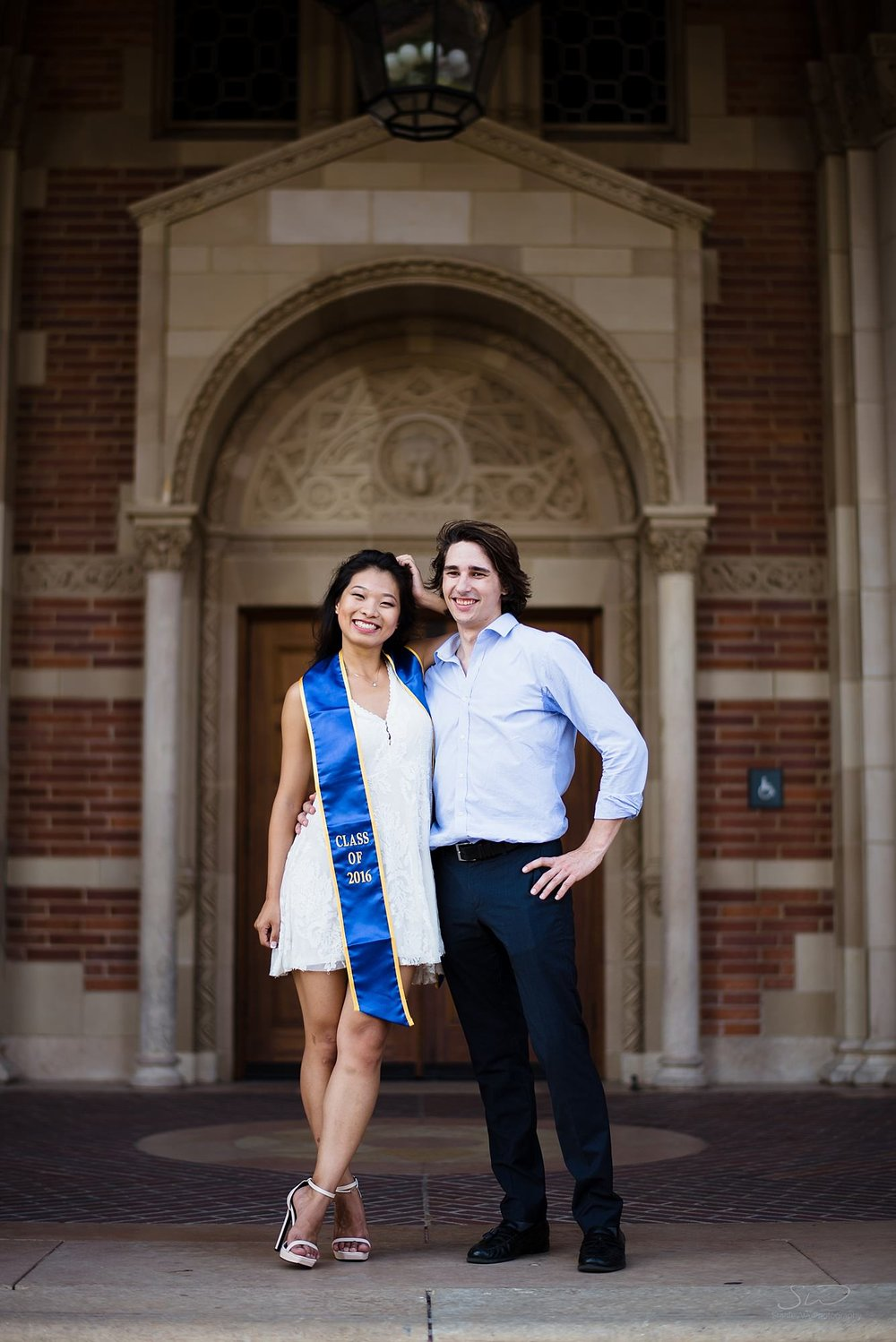 cute graduation senior portrait of beautiful couple posing together in front of royce hall at ucla in los angeles