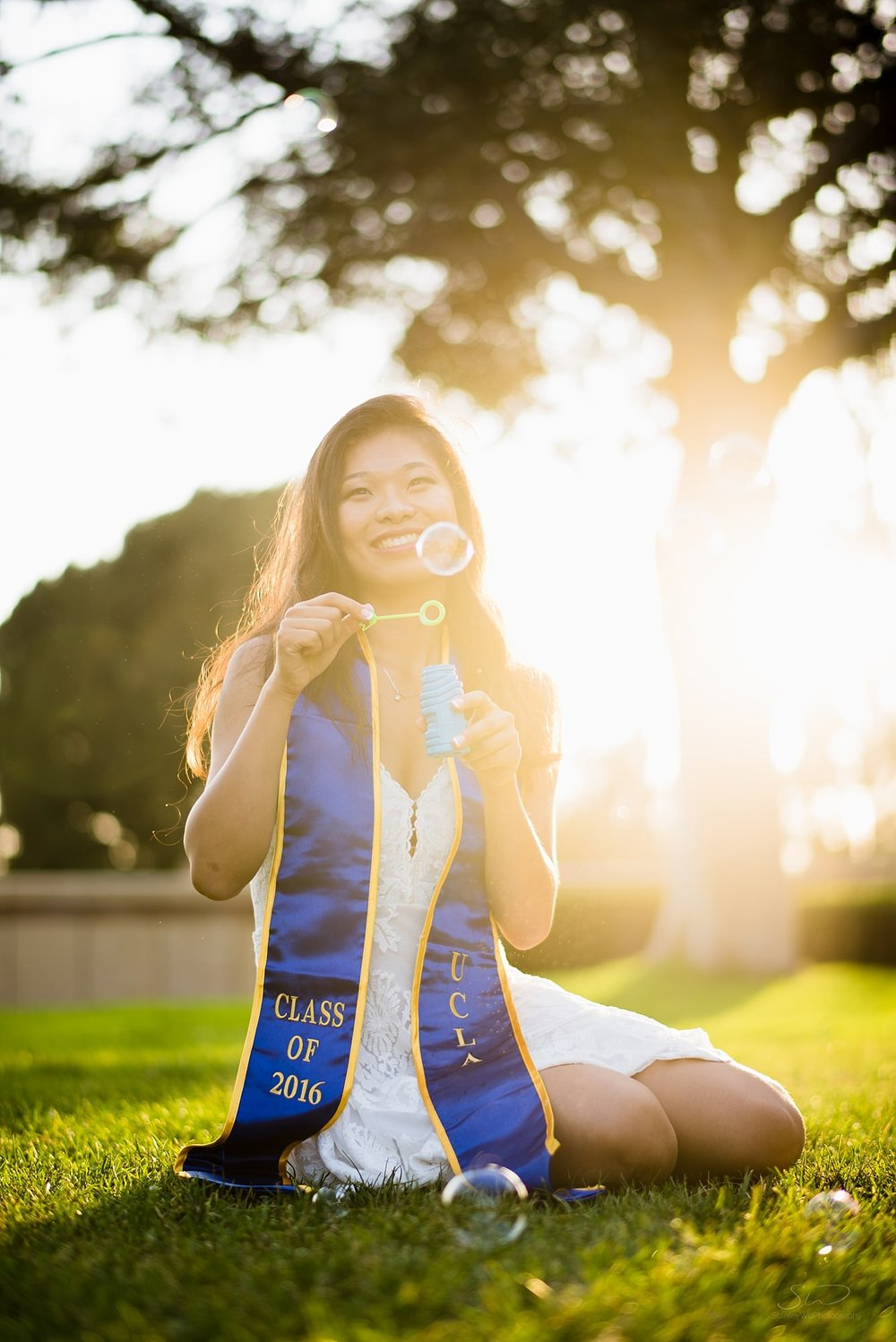 beautiful graduation senior portrait of a girl blowing bubbles in front of a golden sunset background with a big tree at ucla in los angeles