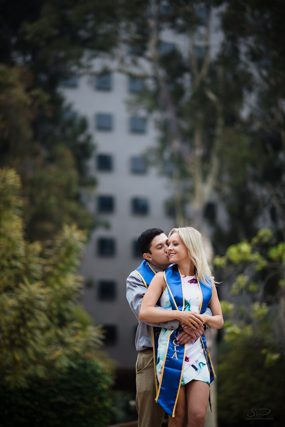 beautiful and epic graduation senior portrait of a couple embracing on steps with a compressed background of bunche hall at ucla in los angeles