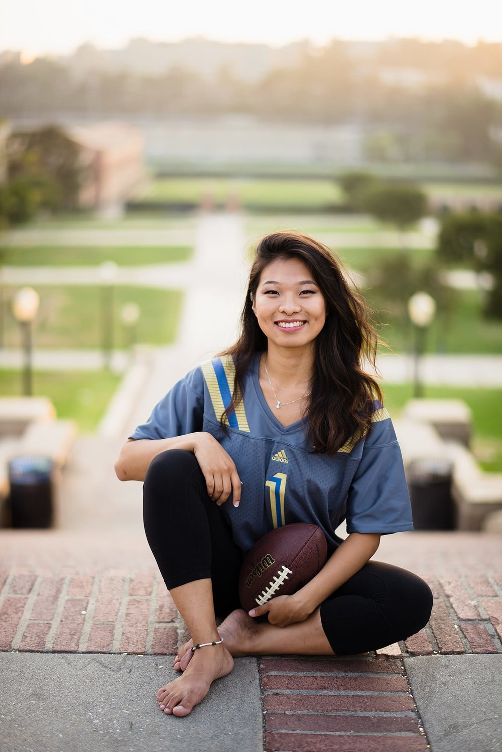 beautiful graduation senior portrait of a girl sitting posed in her football themed outfit on top of janss steps in front of a beautiful sunset at ucla in los angeles