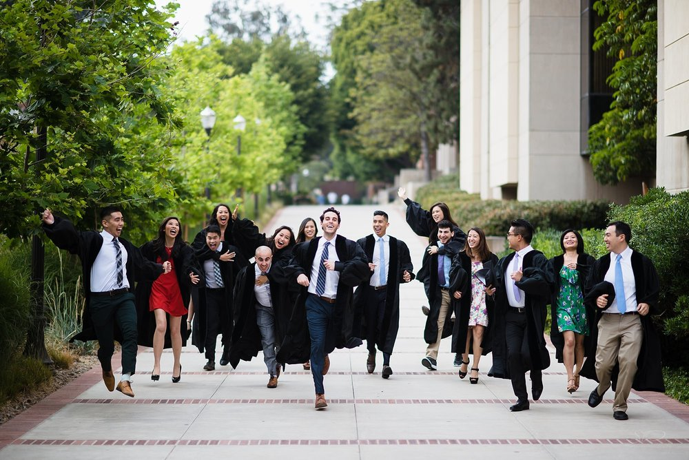 graduation senior portrait of a group of school of dentistry students in graduation gowns running at the camera and having fun at ucla in los angeles
