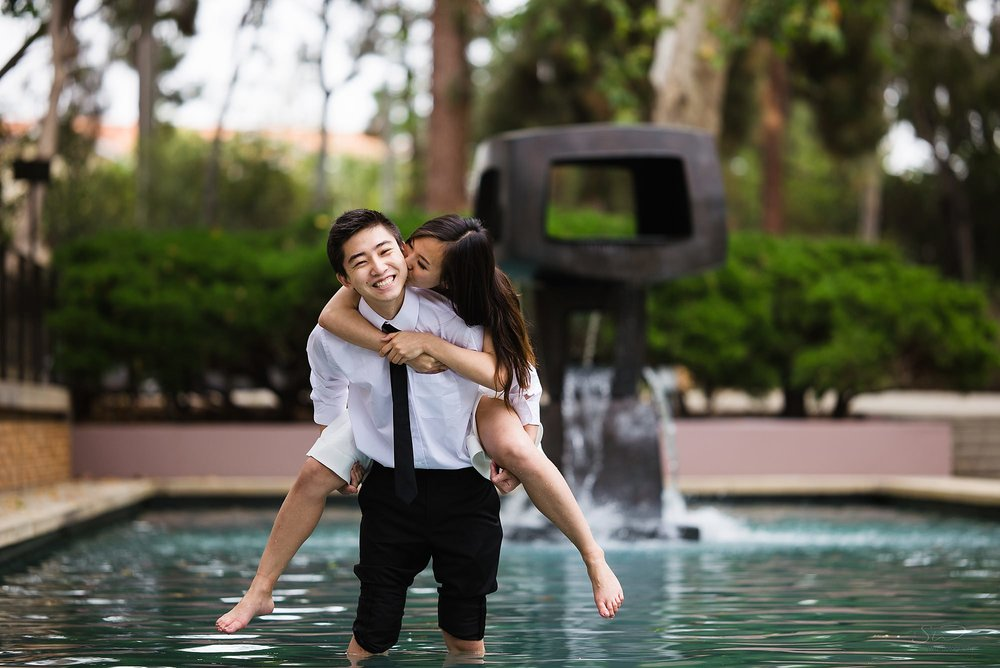 los angeles graduation senior portrait cute couple giving piggyback ride in fountain at ucla