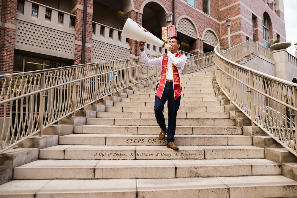 USC college senior graduate walking down steps of Troy holding spirit team sports prop by Stanley Wu Photography | Los Angeles Portrait & Wedding Photographer