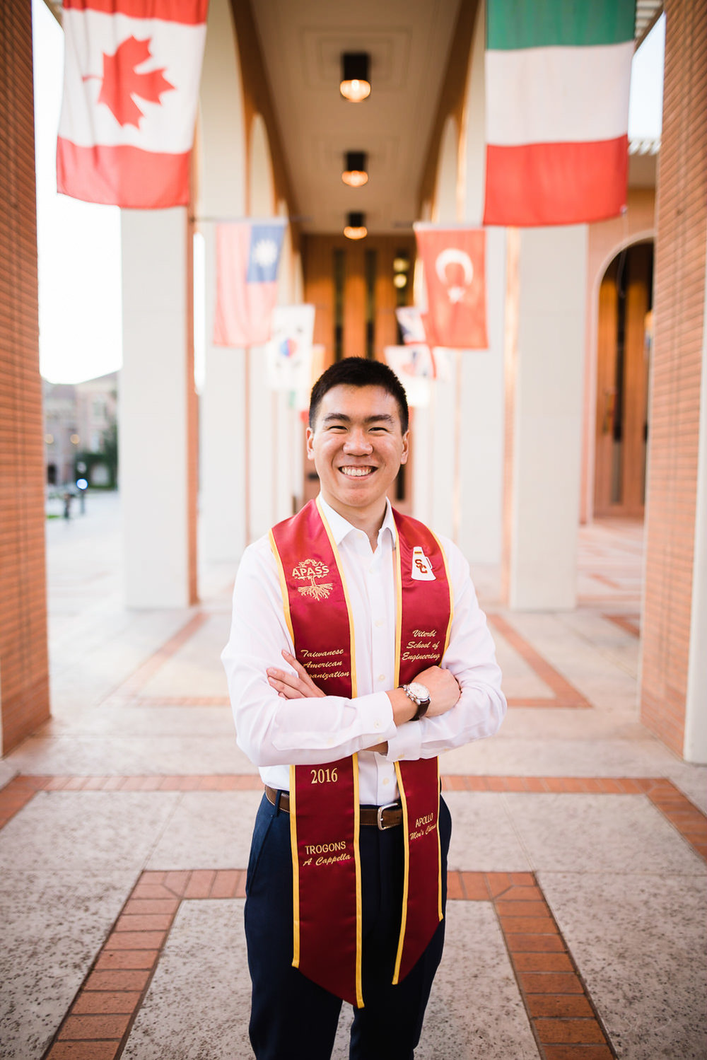 USC college senior graduate standing in front of world flags by Stanley Wu Photography | Portrait & Wedding Photographer serving Los Angeles, Orange County, and Southern California