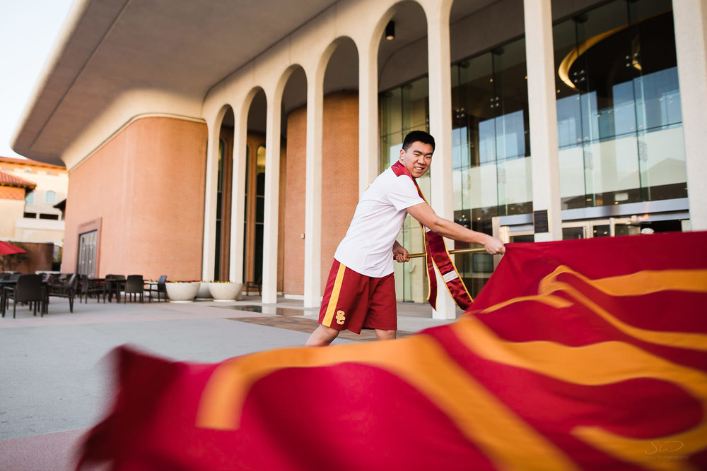 USC college senior graduate waving USC flag by Stanley Wu Photography | Portrait & Wedding Photographer serving Los Angeles, Orange County, and Southern California