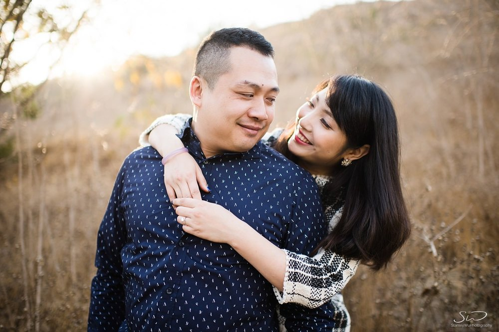 Couple hugging and smiling at each other with sunlight streaming through | Ascot Hills Engagement – Portrait and Wedding Photography by Stanley Wu, based in Los Angeles