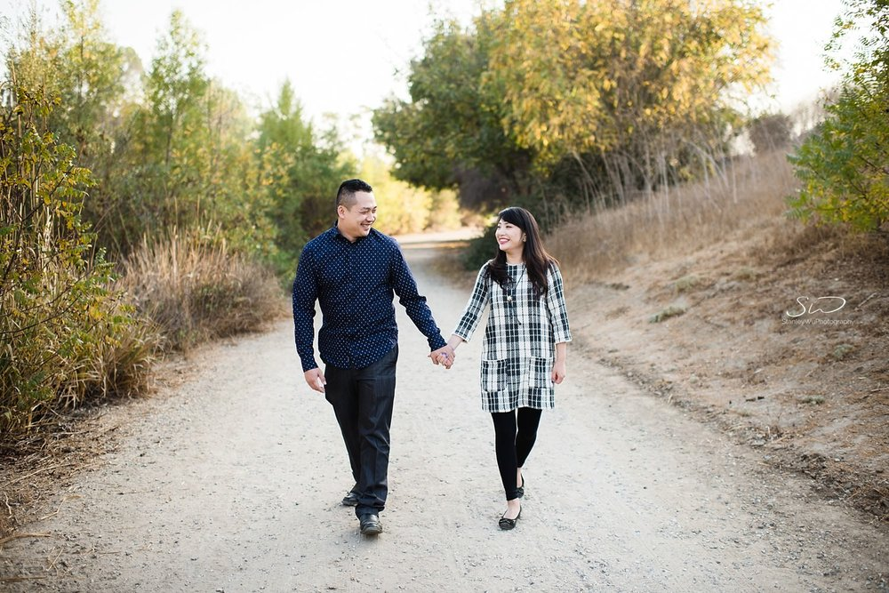 Couple holding hands and walking happily together | Ascot Hills Engagement – Portrait and Wedding Photography by Stanley Wu, based in Los Angeles