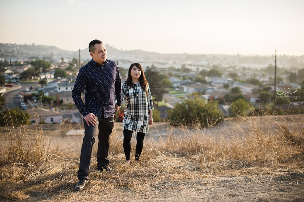 Couple posing heroically upon a sunlit hill | Ascot Hills Engagement – Portrait and Wedding Photography by Stanley Wu, based in Los Angeles
