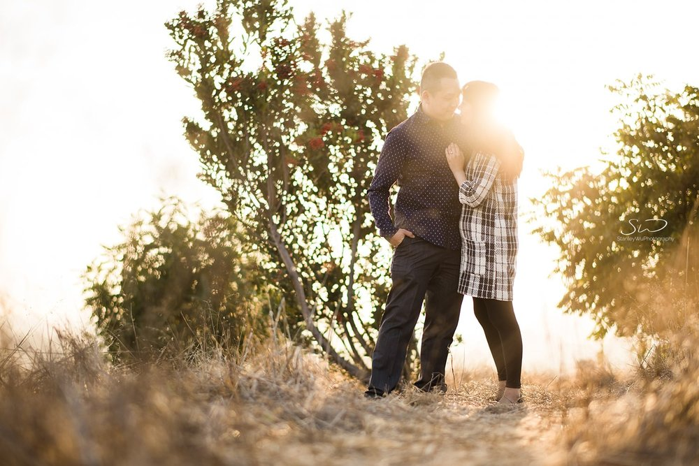 Couple holding each other in front of greenery | Ascot Hills Engagement – Portrait and Wedding Photography by Stanley Wu, based in Los Angeles