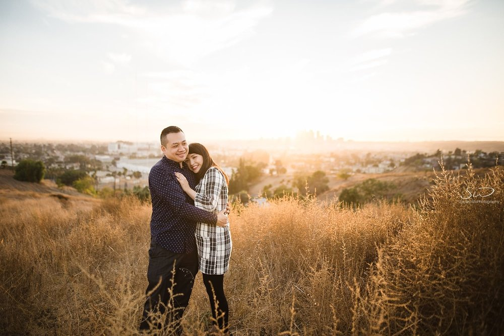 Beautiful sunset portrait of couple holding each other on a hill by Stanley Wu, timeless and artistic portrait and wedding photographer based in Los Angeles.