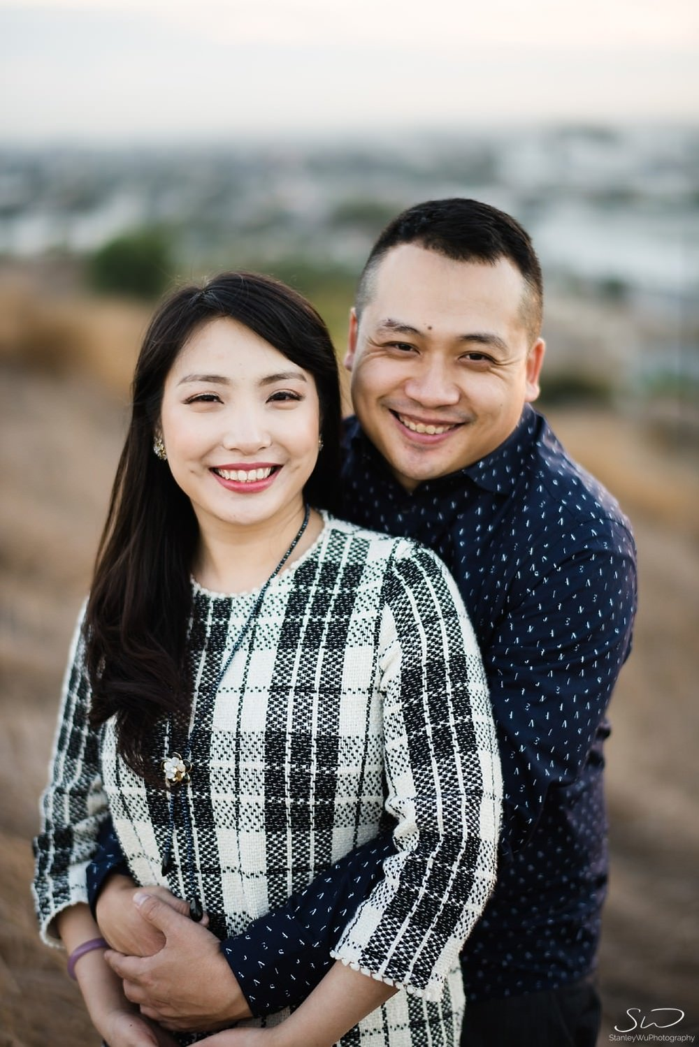 Couple holding each other posing in front of camera  by Stanley Wu, timeless and artistic portrait and wedding photographer based in Los Angeles.