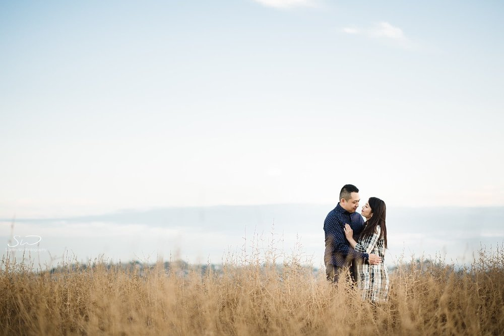 Couple holding each other in a field  by Stanley Wu, timeless and artistic portrait and wedding photographer based in Los Angeles.