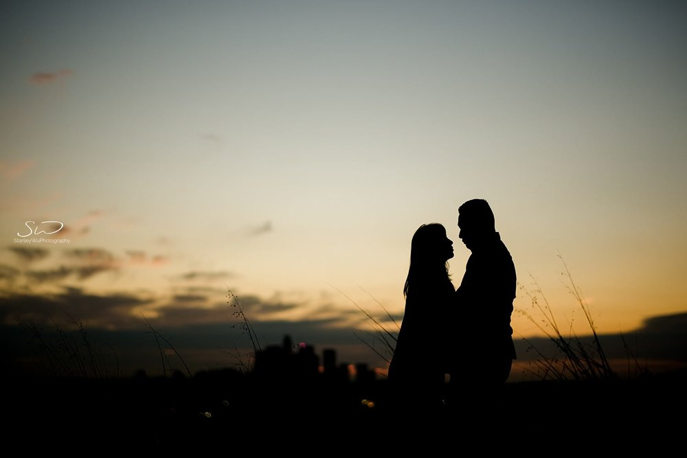 Silhouette shot of couple looking at each other in front of LA skyline by Stanley Wu, timeless and artistic portrait and wedding photographer based in Los Angeles.