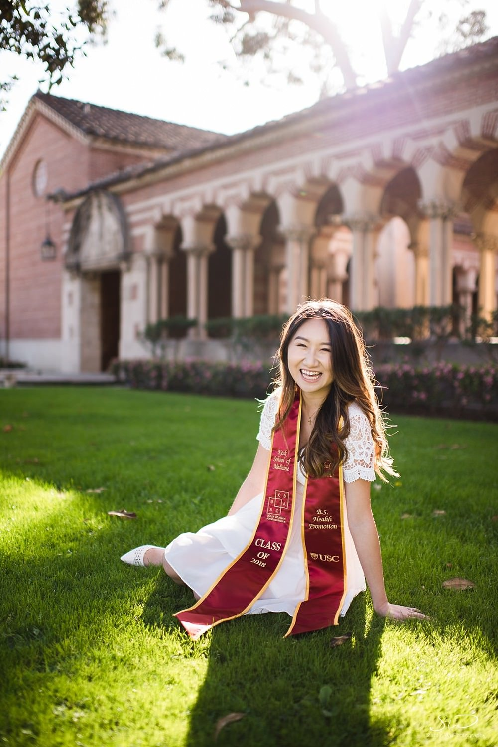 Senior sitting with graduation sash on grass at Mudd Hall at USC | Los Angeles Orange County Senior Portrait & Wedding Photographer