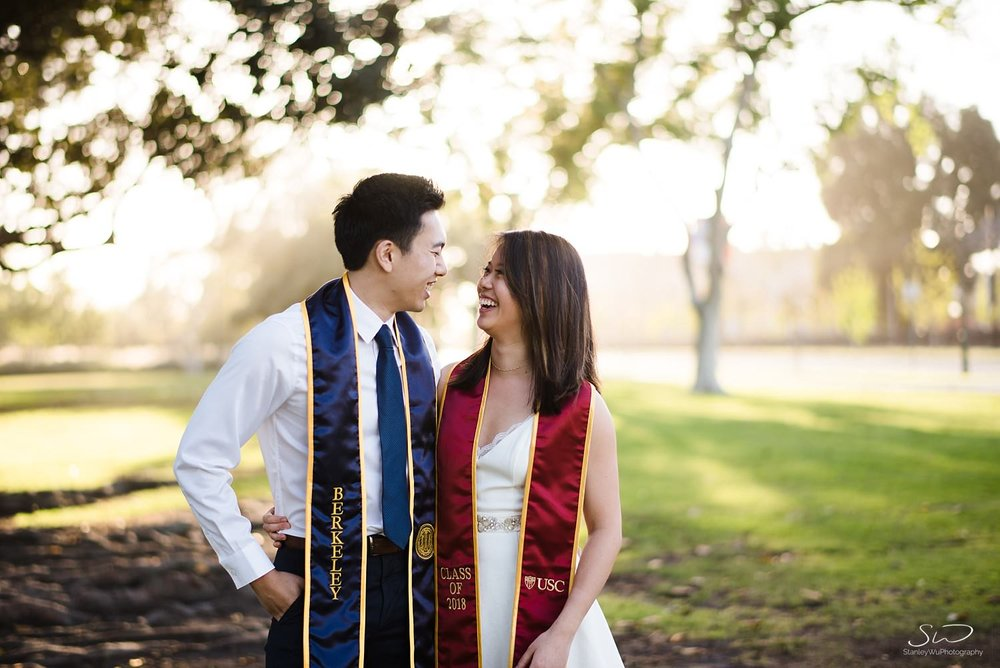 Couple from USC and UC Berkeley wearing sashes smiling at each other | Los Angeles Graduation and Senior Portrait Photographer