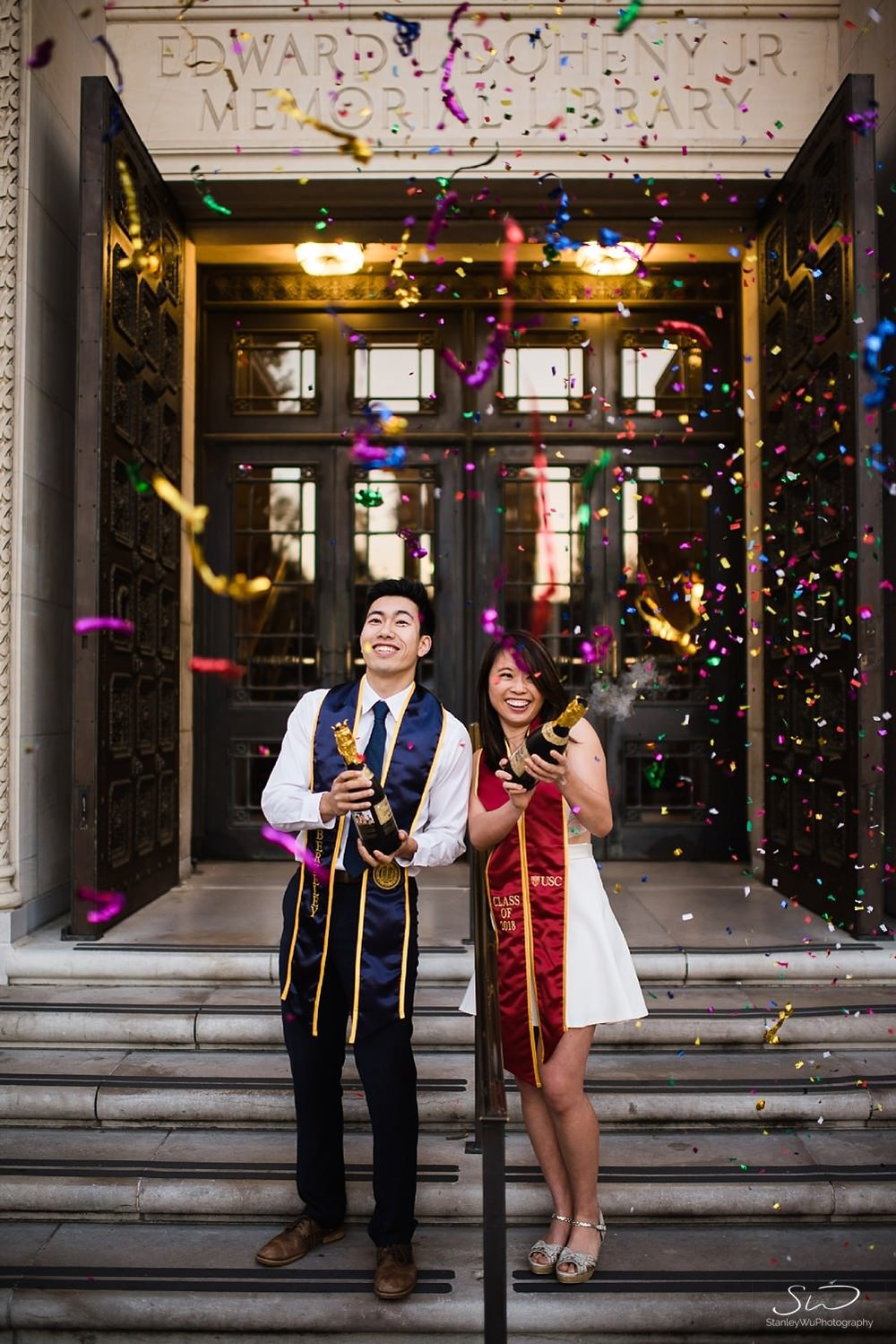 UC Berkeley and USC couple popping champagne confetti in front of Doheny Library USC | Los Angeles Graduation and Senior Portrait Photographer