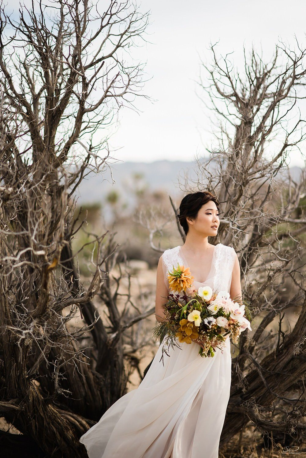 Bride with desert wedding bouquet | Joshua Tree Desert Wedding & Engagement Inspiration