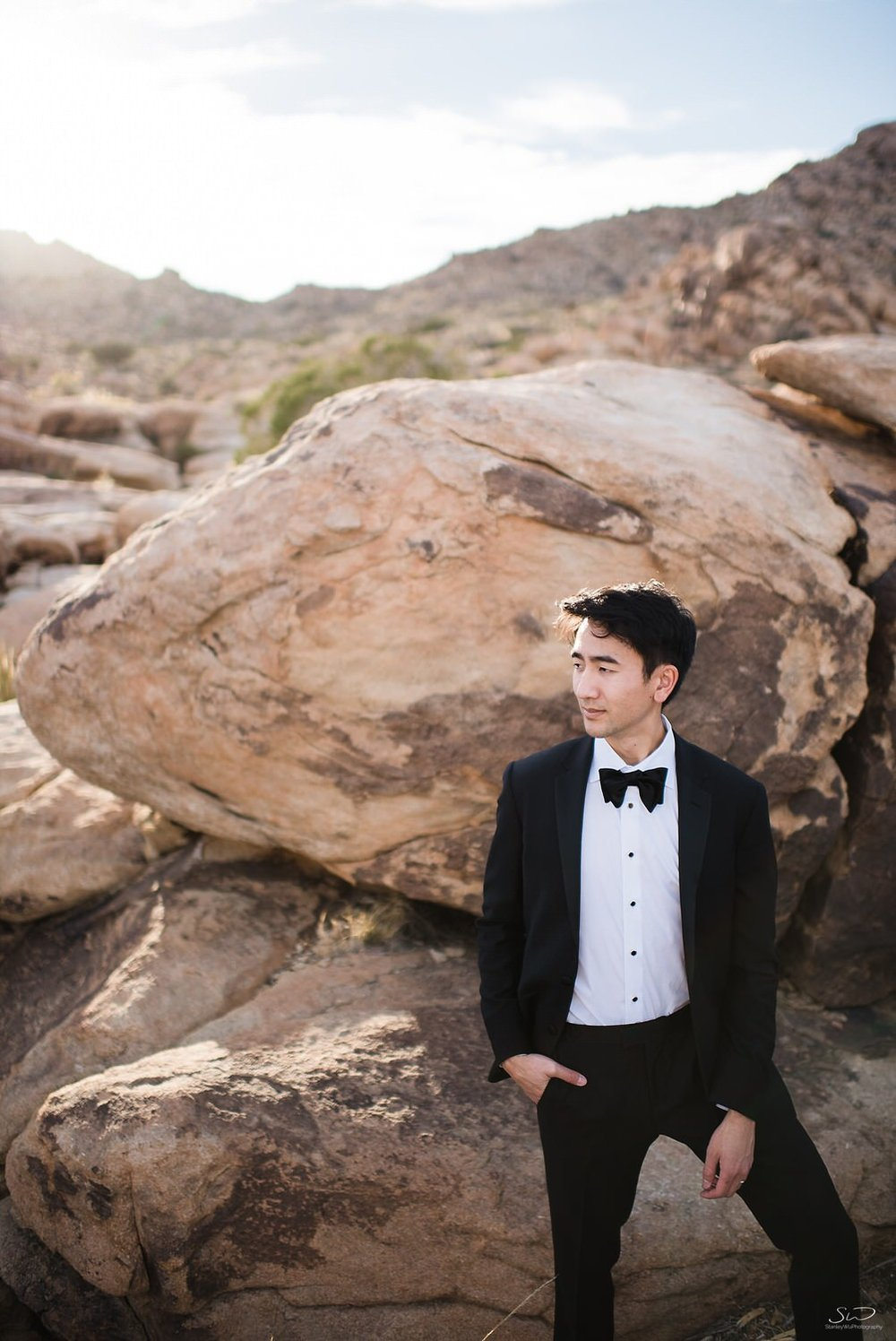 Groom in tux posing on rocks | Joshua Tree Desert Wedding, Engagement, Elopement Inspiration