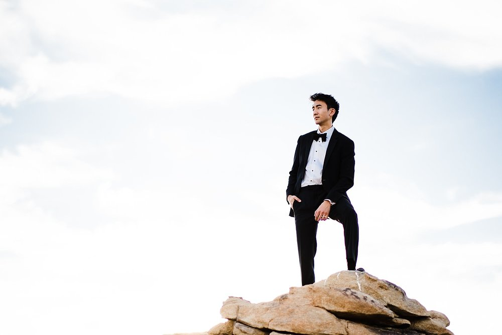 Groom in tux posing on rocks | Joshua Tree Desert Wedding, Engagement, Elopement, Adventure Inspiration