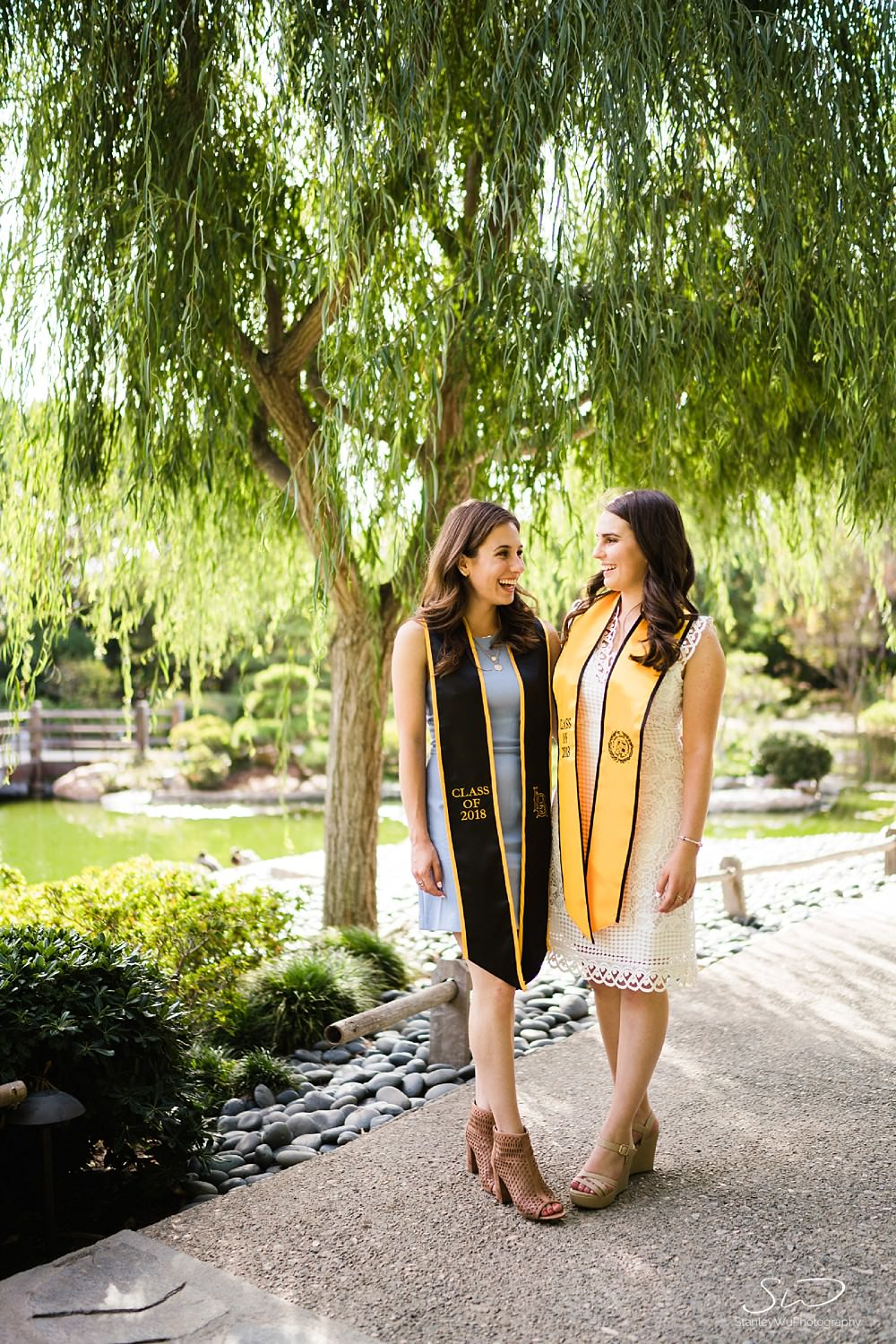 two girls smiling laughing under a tree two girls smiling graduation portraits at csulb earl burns miller japanese garden