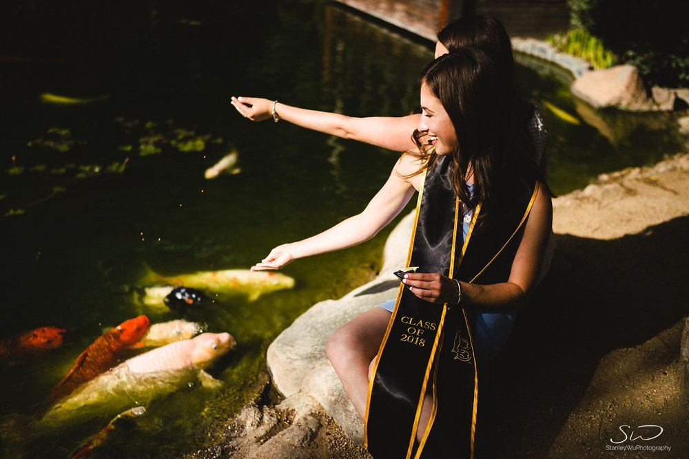two girls feeding koi fish graduation portraits at csulb earl burns miller japanese garden