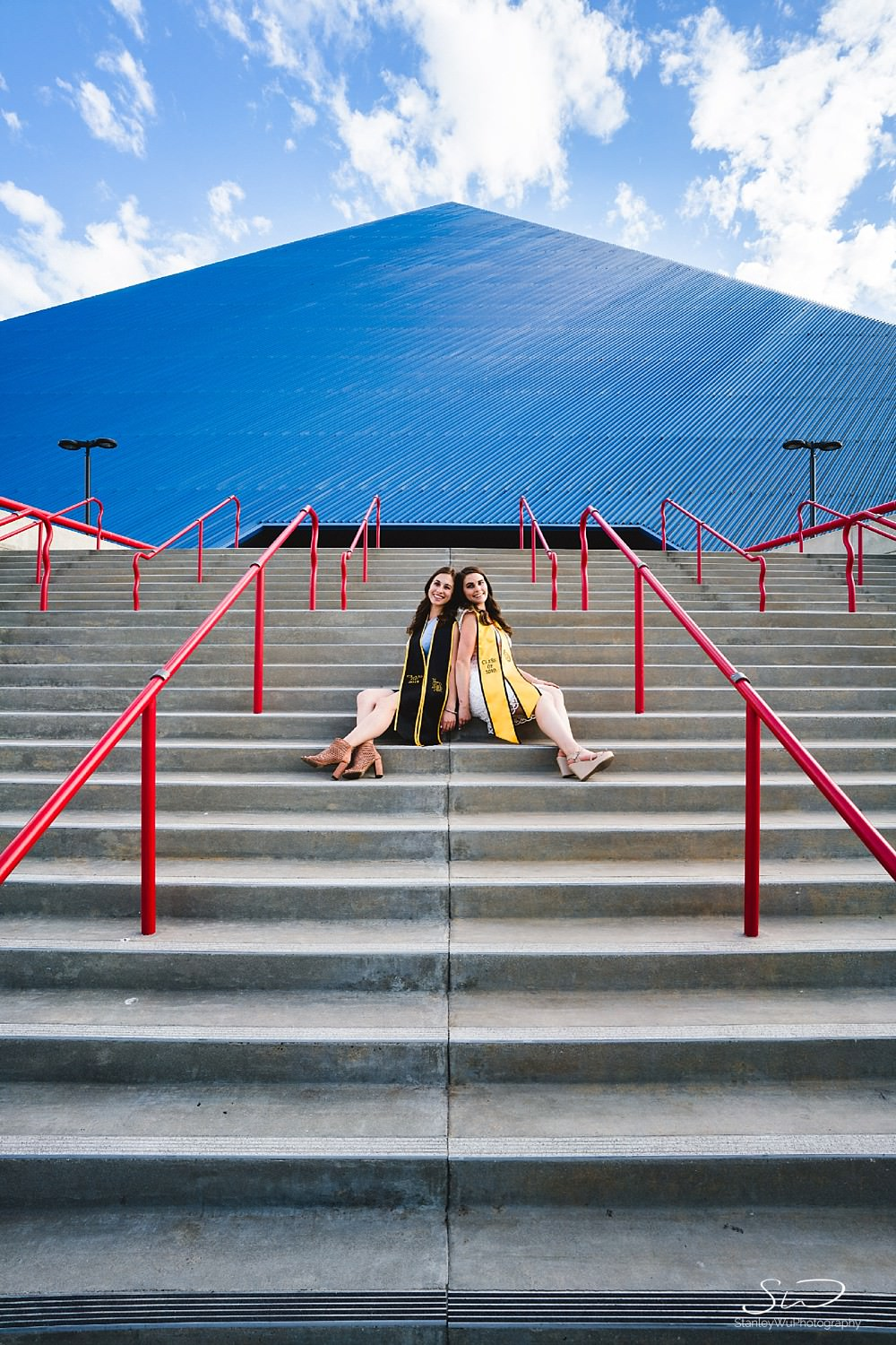 twin sisters sitting graduation portraits at csulb pyramid