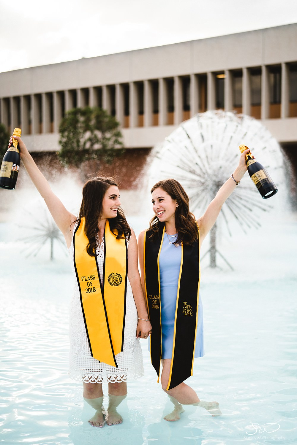 twin sisters with champagne confetti graduation senior photos portraits at csulb