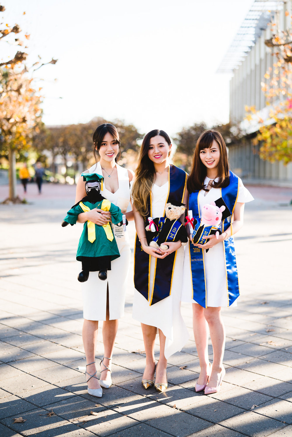 portrait of three girls holding stuffed animals in graduation apparel at ucla and uc berkeley