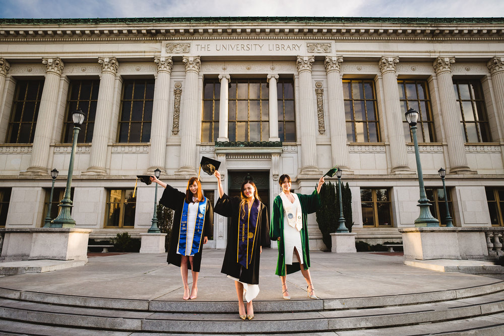 environmental portrait of three graduates holding their caps up at uc berkeley main library