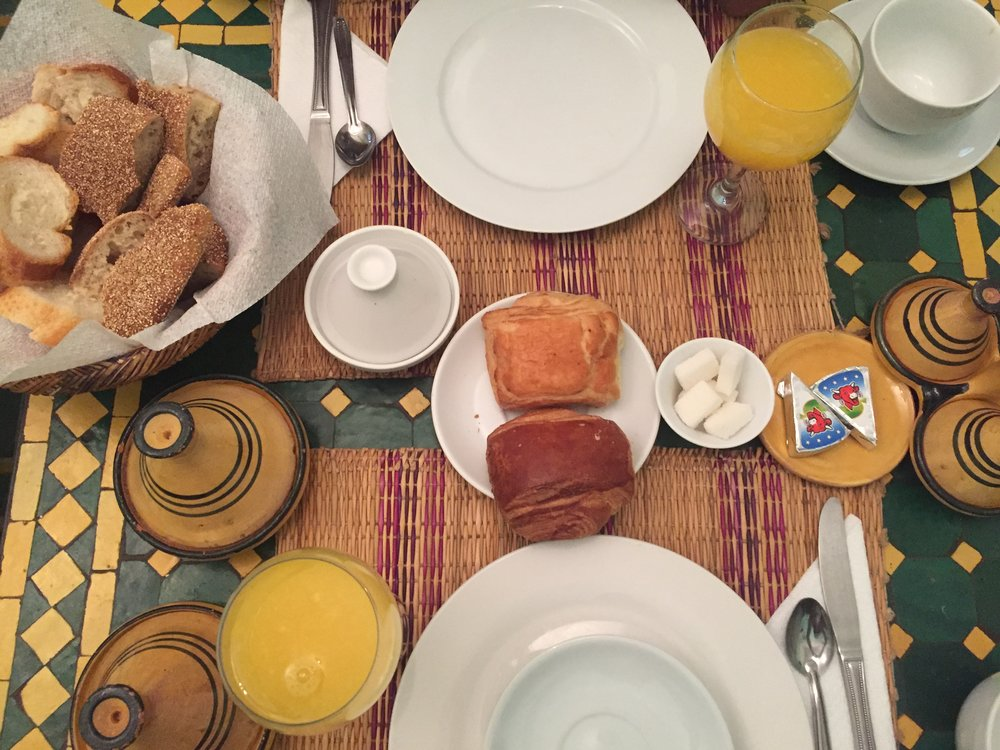 Fancy moroccan breakfast with freshly squeezed orange juice, bread, tea, crepes, jam, cheese.