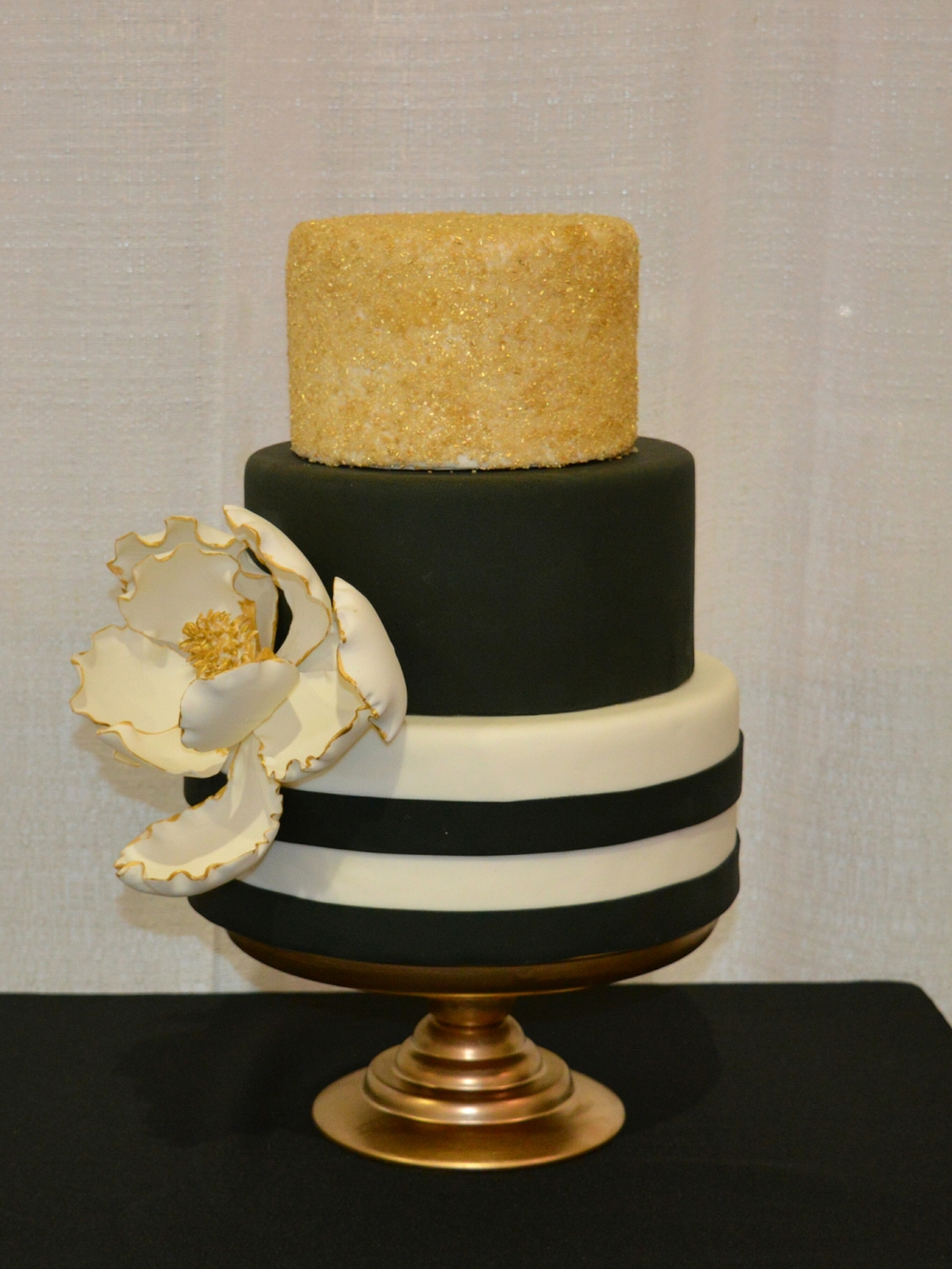 Gold and black wedding cake with sugar magnolia by Sarah Blanchard