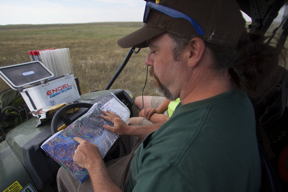 Ry Thompson, left, and Jason Behrends, of Applied Ecological Services, look at a map of the 777 Ranch to plan the next section to test, in Hermosa, SD.
