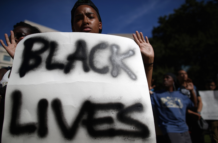 A demonstrator holding a sign during a moment of silence for victims of police brutality, in Oakland, California, Aug. 14, 2014. (Justin Sullivan/Getty Images) Click on the image to view the link.