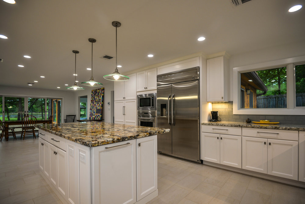 Kitchen remodel in Bryan / College Station, by Stearns Design Build. It feature updated light fixtures, and large windows to also let in light.
