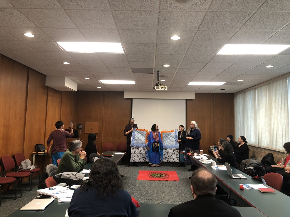 Knowledge Keepers Ed Azure (left) and Florence Paynter (right) hold up the Star Blanket. Catherine Whitecloud stands on the far right.