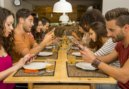 43061868-group-of-friends-at-a-restaurant-with-all-people-on-the-table-occupied-with-cellphones