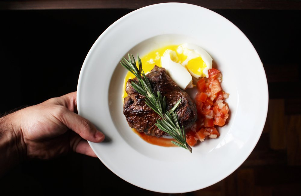 plate of dinner with steak egg and vegetables