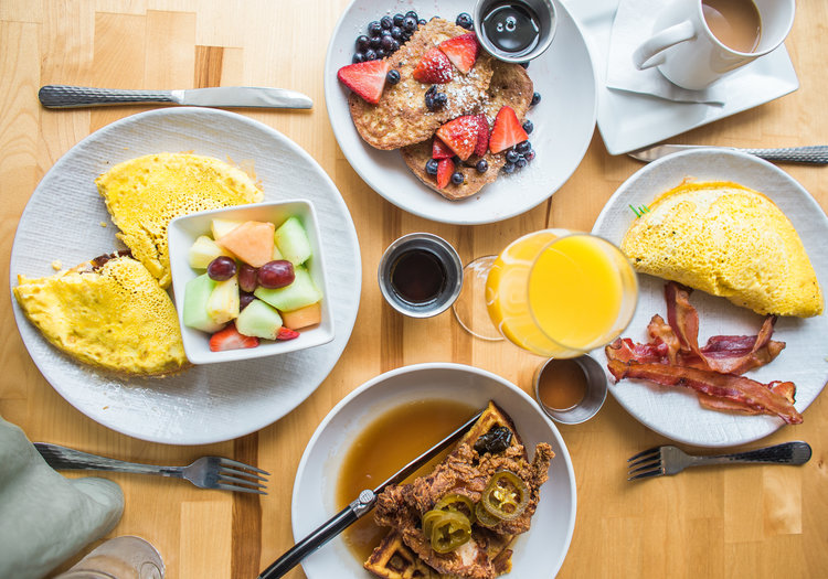 aerial view of a brunch spread with juice pancakes eggs and chicken and waffles