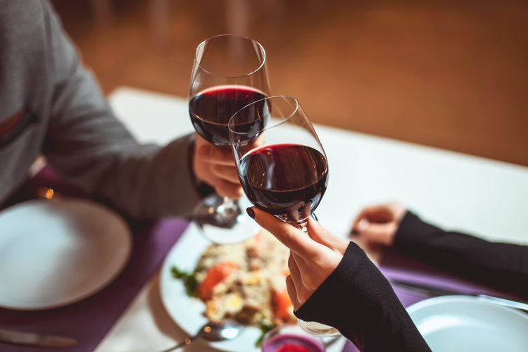 couple cheers with red wine at dinner table