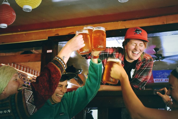 friends watching super bowl game laughing and doing cheers with beer