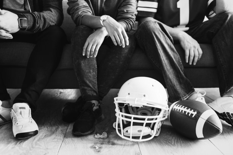 people sitting with football gear helmets and football