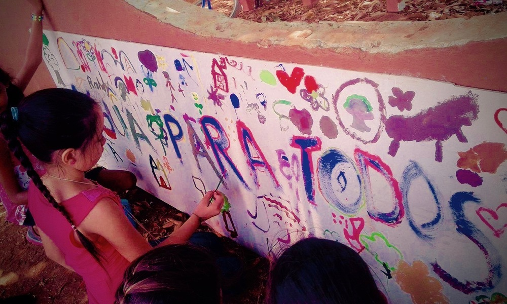 "Kids painting a mural that says ""Agua Para Todos"" or water for everyone."