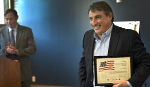 Cascade Management, Inc Portfolio Manager Joe Vennes accepts an award on behalf of his company for providing units to homeless Veterans. Portland City Commissioner Dan Saltzman looks on.