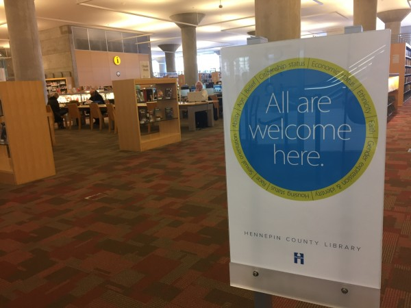 "Image of a sign at the Hennepin County Library that says ""All are welcome here."" Via School Library Journal"