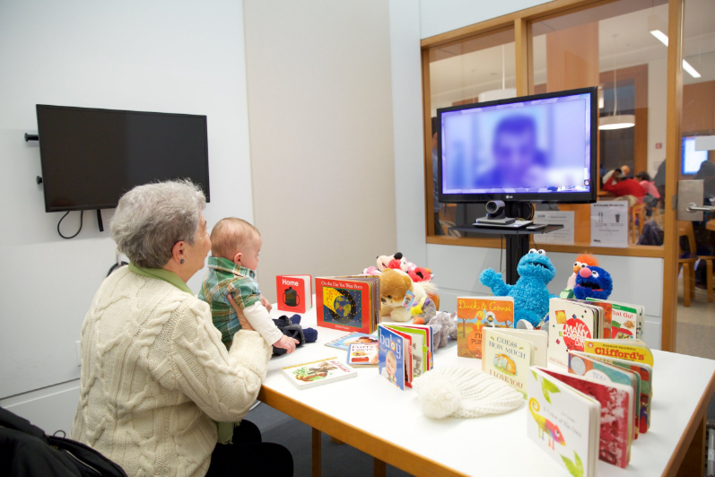 Image of an adult holding a baby up to a TV screen. The child is interacting with their incarcerated parent through the screen and there are numerous books and toys in front of the baby. Via Brooklyn Public Library