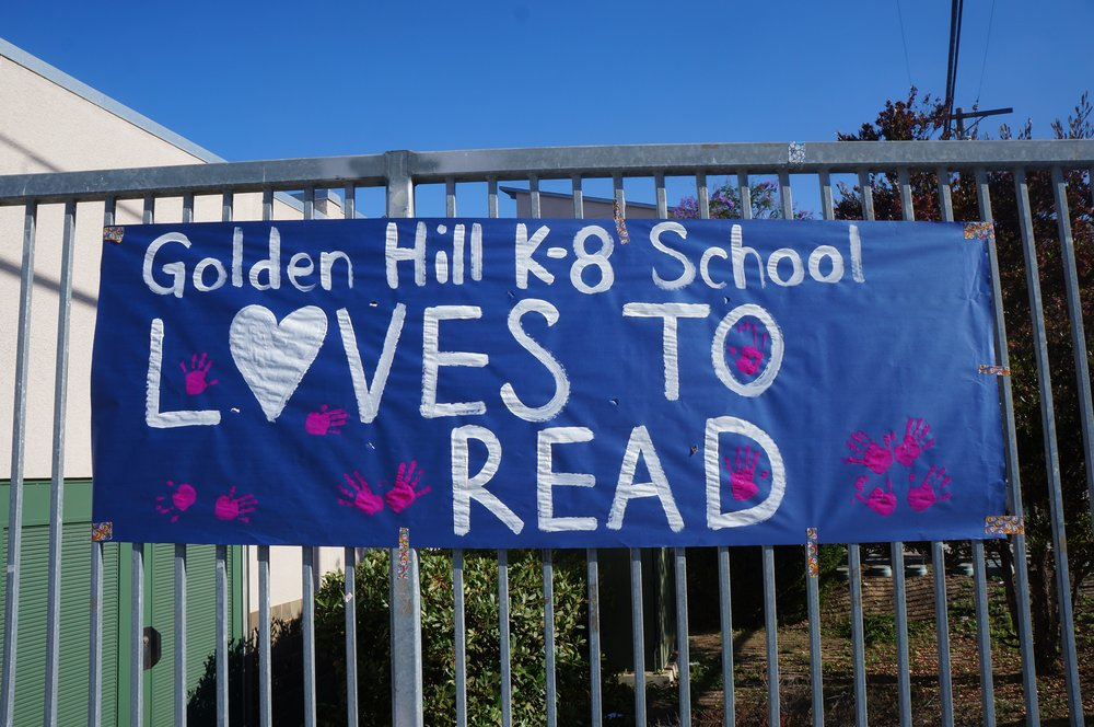 "The students at Golden Hill made a sign for the giveaway event. It says ""Golden Hill K-8 School Loves to Read!"""