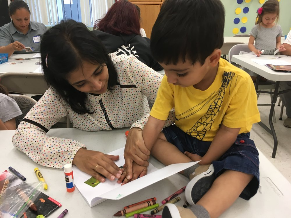 A picture of a parent and child working together on an exercise in our Family Literacy Program. The child is sitting on top of the table while working, showing how we emphasize play and comfort in literacy education!