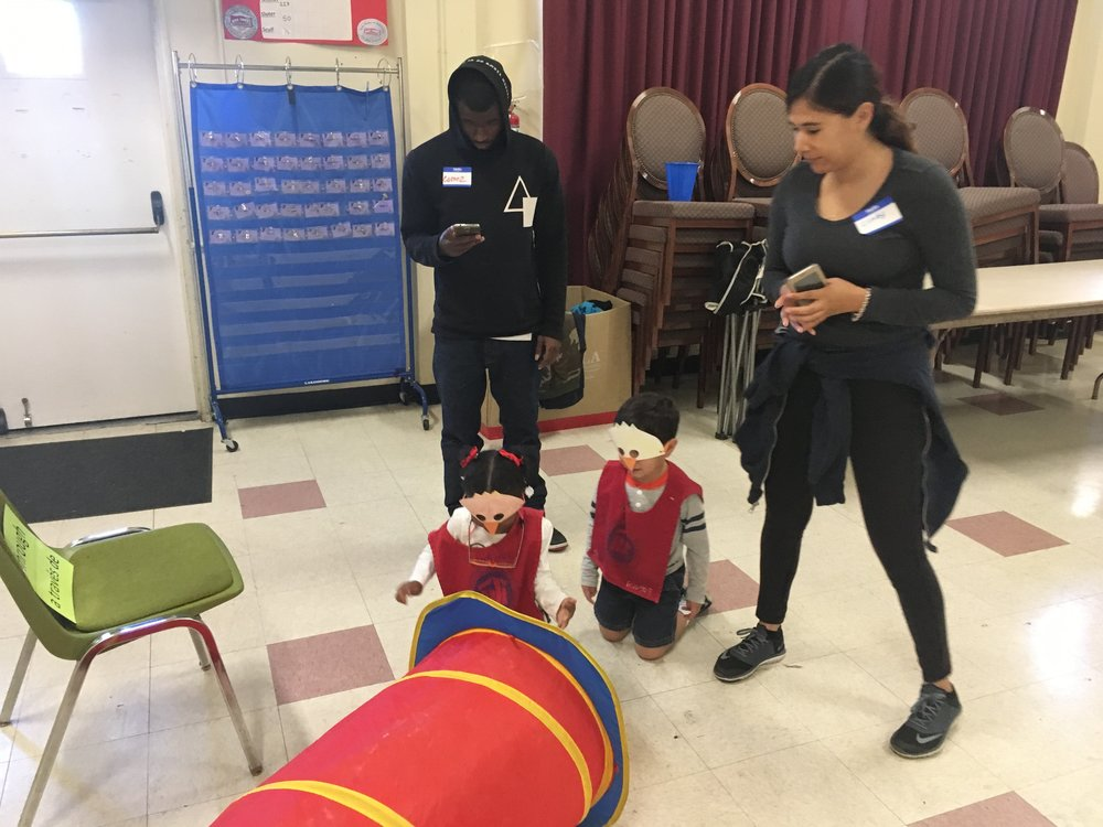 "Another example of teaching with play! Two students learn terms like ""through"" by crawling through a tunnel at one of our Family Literacy sites."