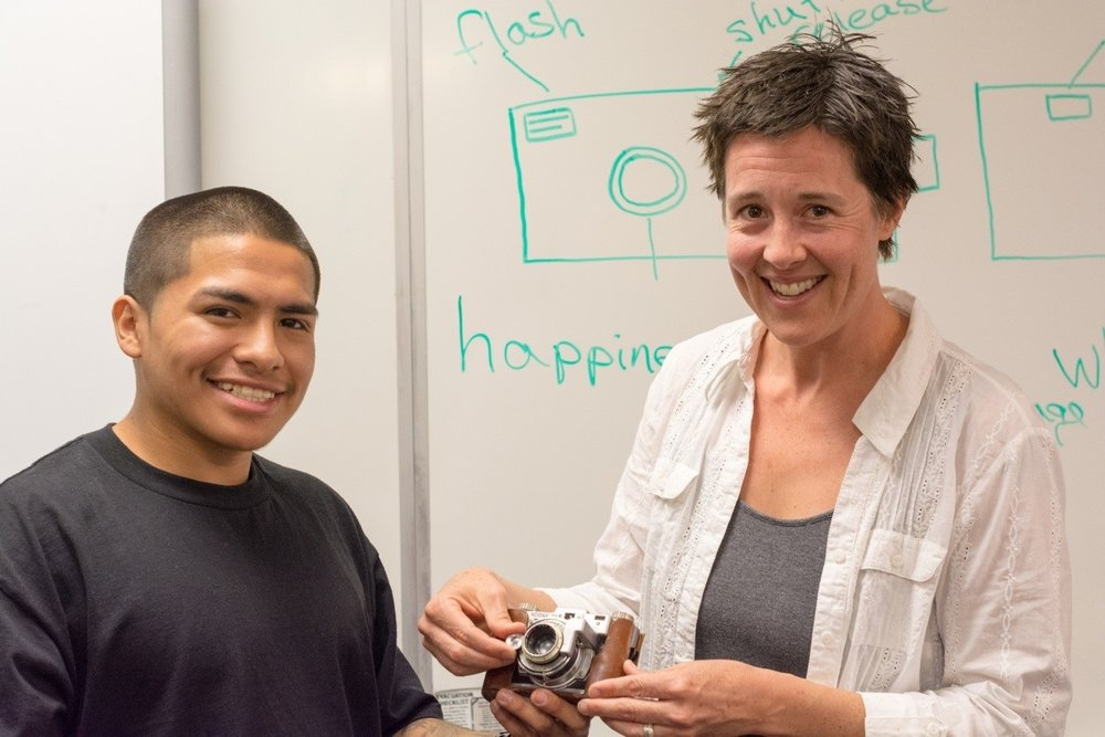 A teacher and student holding a camera together during our Arts Component focused on photography.